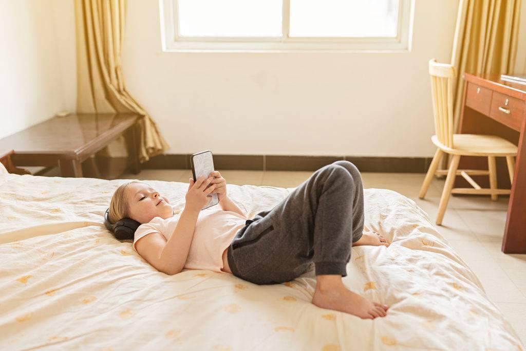 Bambina sul letto con cellulare in mano