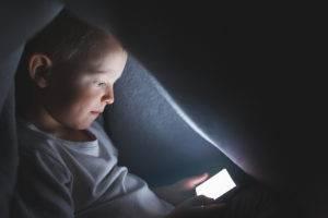 Bambino sotto le coperte mentre gioca con uno smartphone