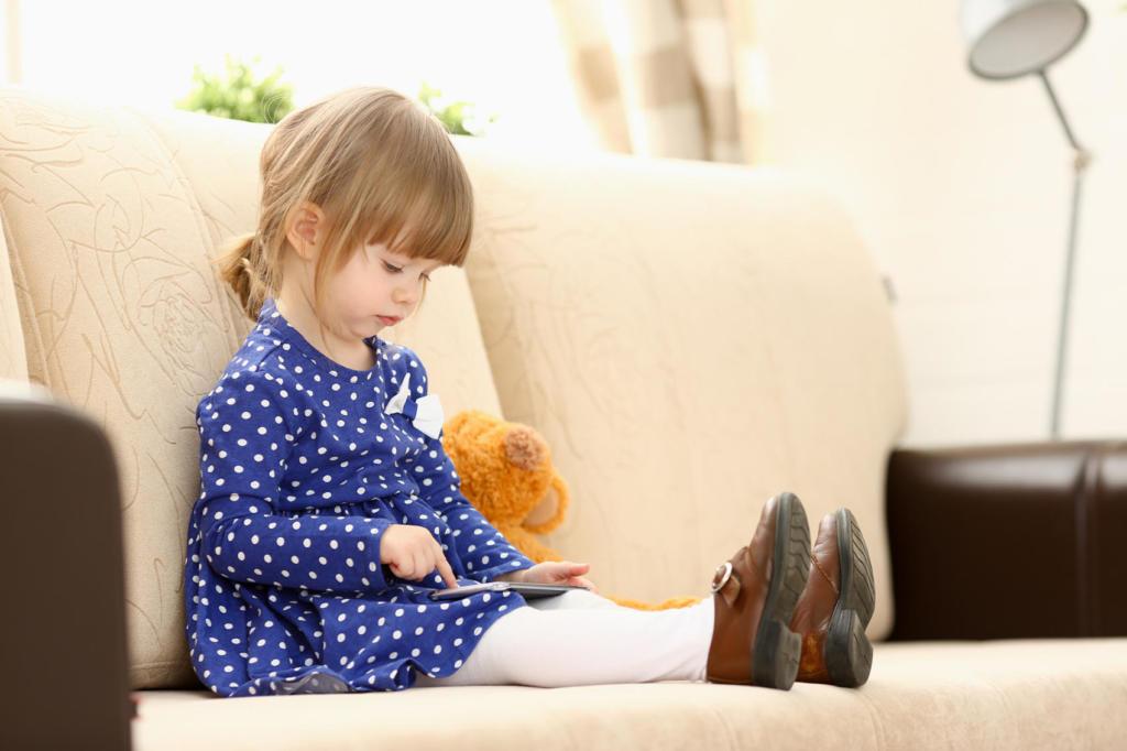 Bimba sul divano con smartphone